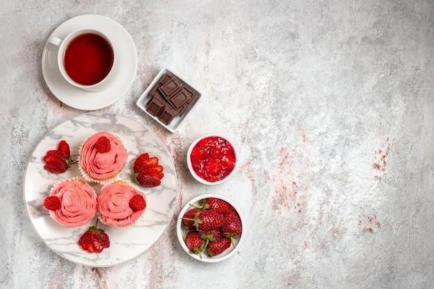 Vista dall'alto di torte alla fragola rosa con crema e tazza di tè sulla superficie bianca