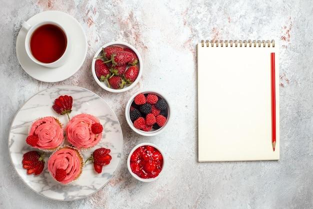 Vista dall'alto di torte alla fragola rosa con una tazza di tè sulla superficie bianca