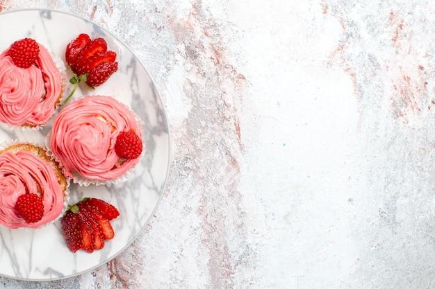 Vista dall'alto di torte di fragole rosa con fragole rosse fresche su superficie bianca chiara
