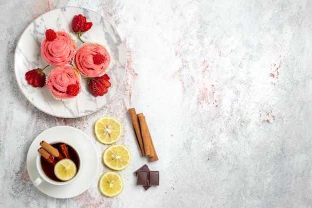 Vista dall'alto di torte di fragole rosa con fragole rosse fresche su superficie bianca