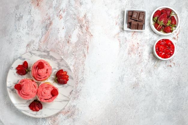 桃红色草莓蛋糕顶视图用果酱和巧克力块在白色表面上