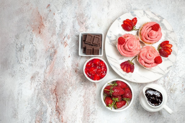 Top view of pink strawberry cakes with jam on white surface