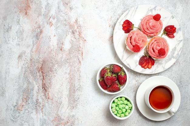 Vista dall'alto di torte di fragole rosa con tè sulla superficie bianca