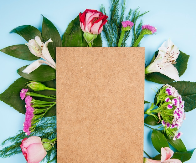 Vista dall'alto di rose rosa e bianche e fiori di alstroemeria con garofano turco e statice con un foglio di carta marrone su sfondo blu