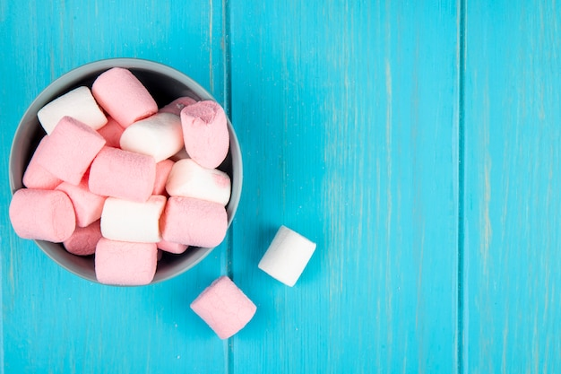 Top view of pink and white marshmallow in a bowl on blue