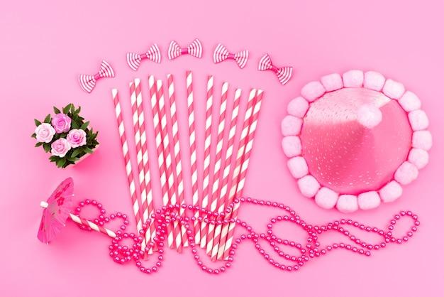 Una vista dall'alto caramelle rosa-bianche in stick insieme a un berretto di compleanno rosa carino, fiocchi rosa, colore del compleanno