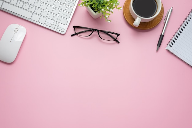 Top view of pink workspace with coffee keyboard notebook glasses copy space paste flat.