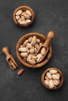 Вид сверху фисташковые орехи в мисках с деревянными ложками