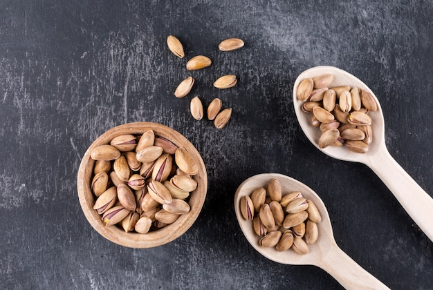 Top view pistachios in a bowl and wooden spoons on gray texture  horizontal