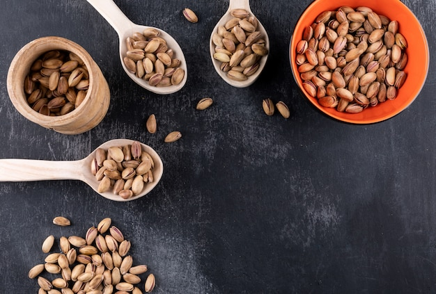 Top view pistachioswith copy space in bowl and wooden spoons on gray texture  horizontal