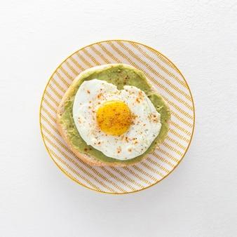 Вид сверху лаваш с авокадо и жареным яйцом на тарелке