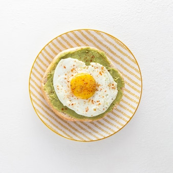 Top view pita with avocado and fried egg on plate