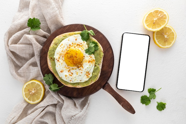 Top view pita with avocado spread and fried egg with blank phone