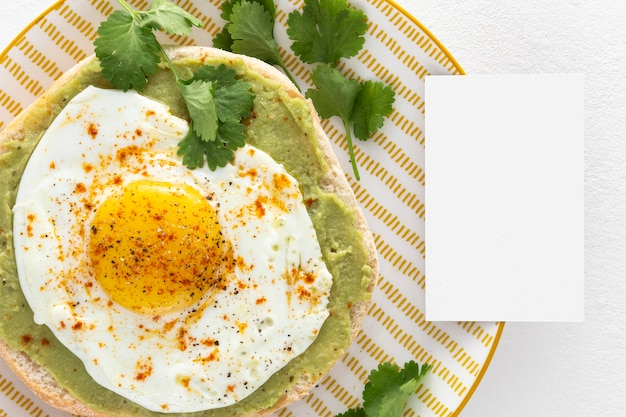 Top view pita with avocado spread and fried egg  with blank rectangle