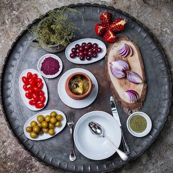 Вид сверху пити в глиняном горшочке с оливками и луком и гранатом в медном подносе