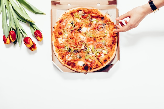 Top view of a pizza in a box, tulips and a female hand on a white background