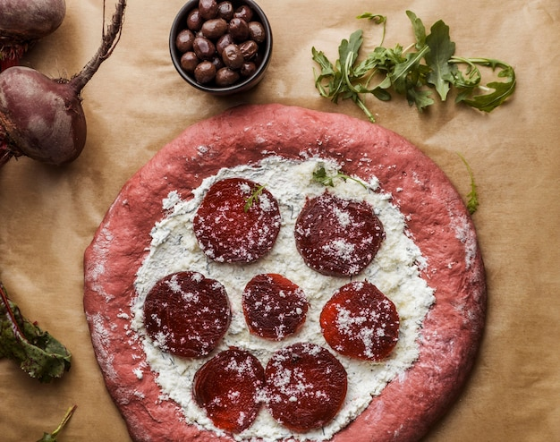 Top view of pizza dough with beet slices