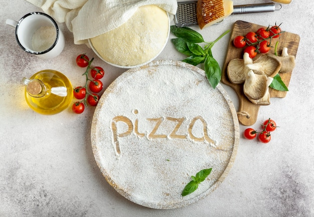 Top view of pizza dough with mushrooms and tomatoes and word written in flour