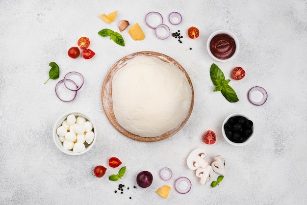 Top view pizza dough with vegetables