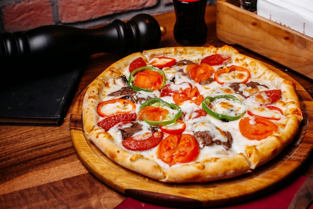 Top view of pizza filled with tomatoes colorful bell peppers salami and olives on a wooden board
