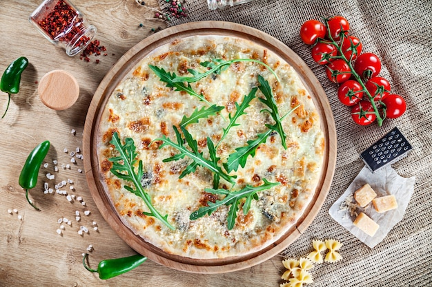 Top view pizza four cheese with arugula on wooden background. italian cuisine. snack and fast food. food photo horizontal. pizza with ingridients on table. delicious pizza with copy space