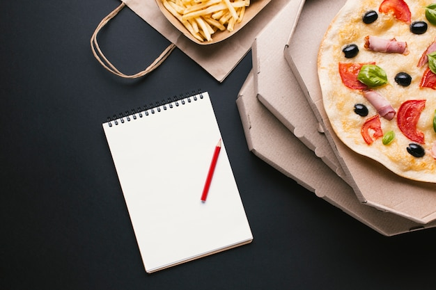 Top view pizza and fries with notebook