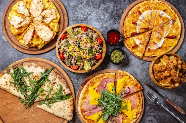 Top view pizza mix ham and cheese pizza calzone pizza with arugula french fries pizza with grilled chicken breast bacon pizza with deep fried chicken tenders french frie