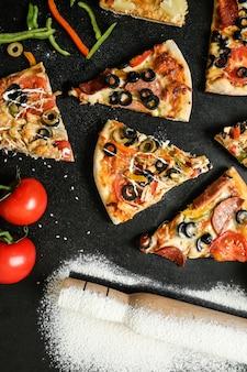 黒いテーブルにトマトオリーブとピーマンの上面ピザミックス