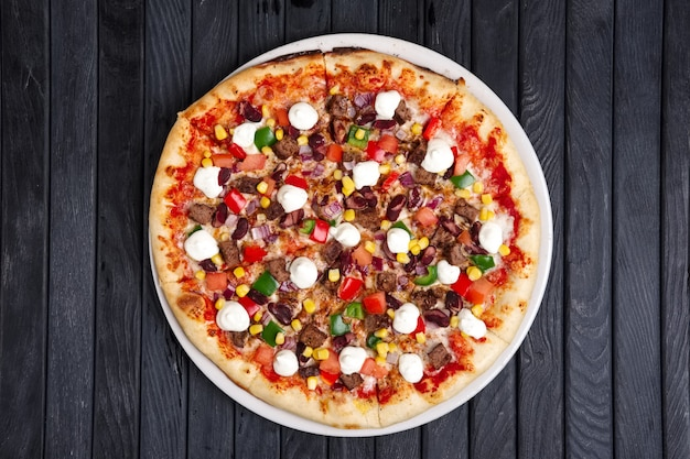 Top view of pizza with beef, feta cheese, bell pepper, corn and onion