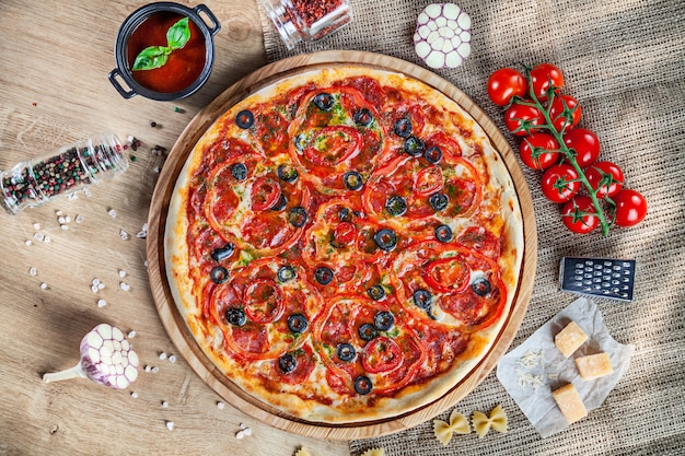 Top view pizza with olive, pepperoni and bell pepper on wooden background. italian cuisine. snack. food photo horizontal. pizza with ingridients on table. copy space, cherry tomato, parmesan, garlic