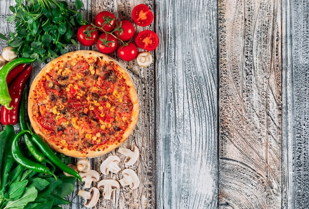 Top view pizza with peppers, mushrooms, tomatoes and grenery on light stucco background. vertical