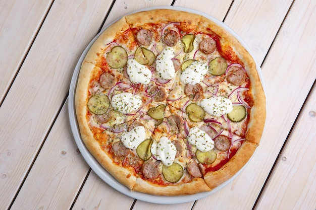 Top view of pizza with sausage, pickled cucumber, melted mozzarella and mushrooms