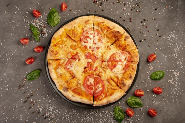 Top view of pizza with tomatoes and pepper