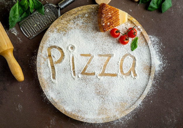 Top view of pizza written in flour with parmesan and tomatoes