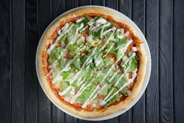 Top view of pizza wth pickled cucumber and salad