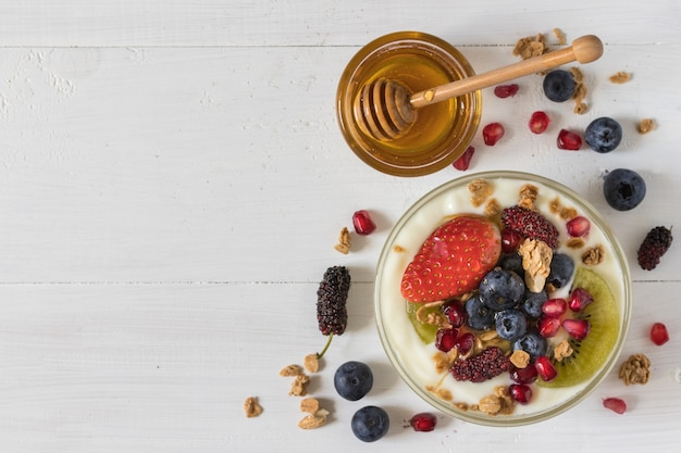 Top view of plain yogurt with strawberry, blueberries, kiwi, granola, pomegranate in a glass bowl and honey