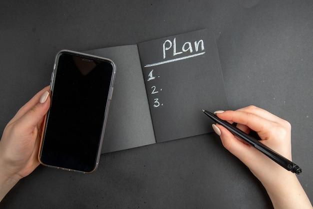Piano vista dall'alto scritto sul telefono con blocco note nero e penna in mani femminili su sfondo nero