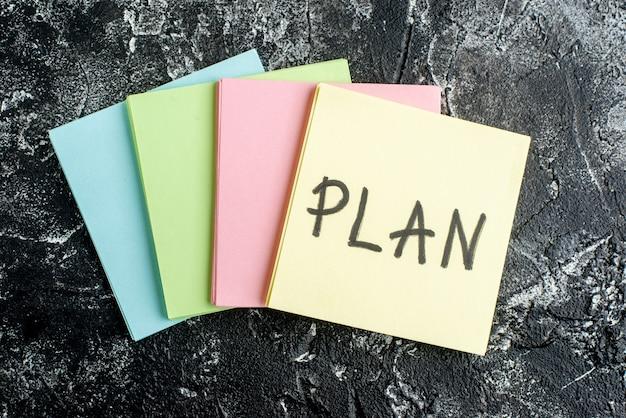 어두운 회색 배경에 다채로운 스티커와 함께 상위 뷰 계획 서면 메모