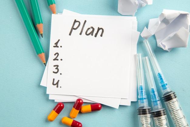 Vista dall'alto piano nota scritta con matite pillole e iniezioni su sfondo blu colore virus pillola salute ospedale covid laboratorio di scienze pandemia