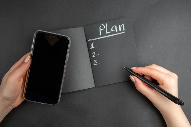 검은색 메모장 전화 및 검정색 배경에 여성 손에 펜으로 작성된 상위 뷰 계획