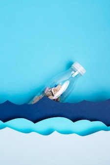 Top view of plastic bottle with paper ocean waves