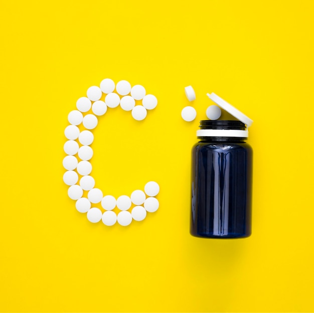 Top view of plastic container and pills spelling letter