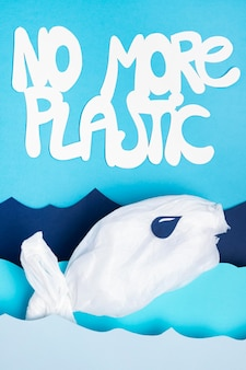 Top view of plastic fish with paper ocean waves and no more plastic