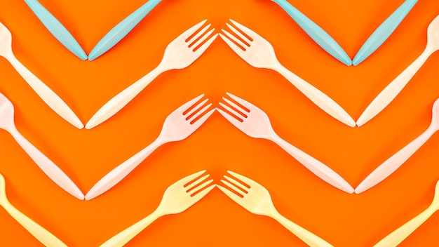 Top view of plastic fork on orange background