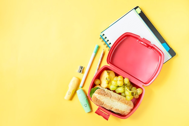 Top view of plastic sandwich box on yellow background with notepad pencils and markers