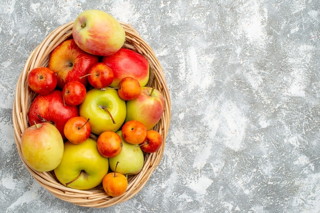 Top view plastic wicker basket with red and yellow apples and plums at the left side of the grey table