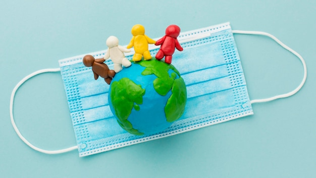 Top view of plasticine earth and people with medical mask