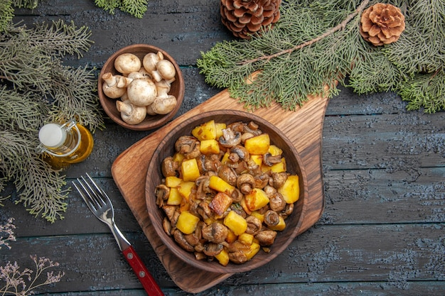 Top view plate on board plate of potatoes mushrooms on wooden board next to the fork under bowl of mushrooms oil in bottle and tree branches with cones