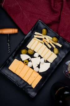 Top view of plate of cheeses as string parmesan and cheddar with olive and corkscrew with cloth on black table