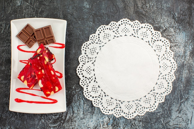 Top view of a plate of chocolate bars and a piece of white lace on grey background